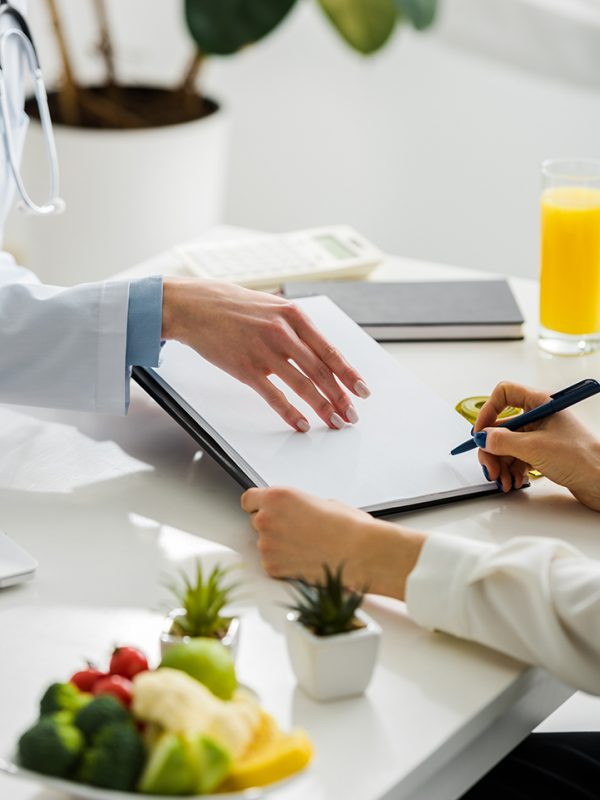 cropped view of nutritionist holding clipboard near patient with pen